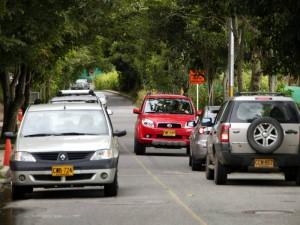 Carros y taxis se parquean sobre uno de los carriles obstaculizando la vía.