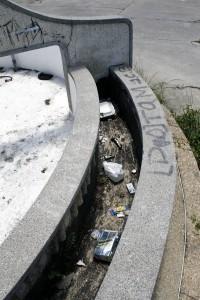 Botellas, cajas y otros tipos de residuos se pueden observar en la fuente.
