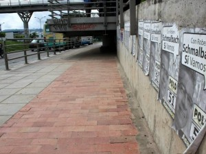 Las paredes de los accesos a los puentes tiene un aspecto sucio con tanto afiche y grafitis.