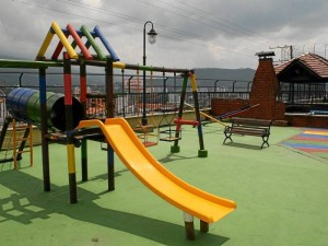 El área de juegos para los niños está completamente impermeabilizada y es bastante amplia. Los colores y columpios se destacan entre los edificios y la zonas verdes.