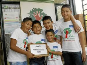 Aquí algunos de los niños de la fundación sostienen la placa que los acredita como 'Héroes Coca Cola'.