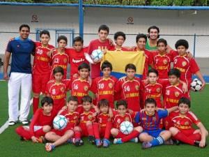El entrenador Adilson (de camiseta azul) acompañado de sus alumnos y el transportador de la escuela, Sergio Rodríguez.