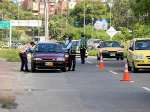 Agentes de tránsito y auxiliares detienen a los conductores para verificar antecedentes.