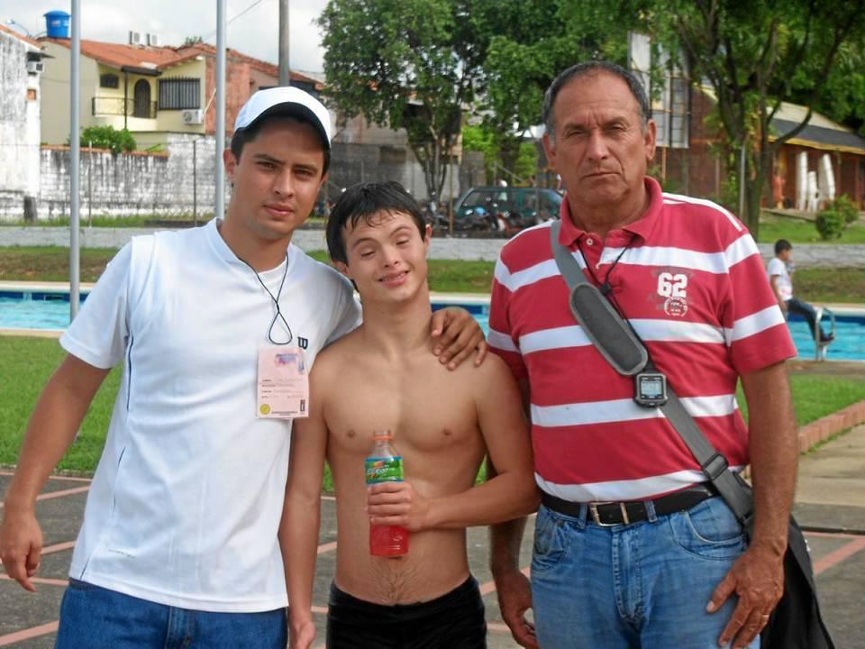 Carlitos posa junto a su entrenador (derecha) William David Jiménez Niño y a su coentrenador y hermano, César Andrés Roa Salazar.