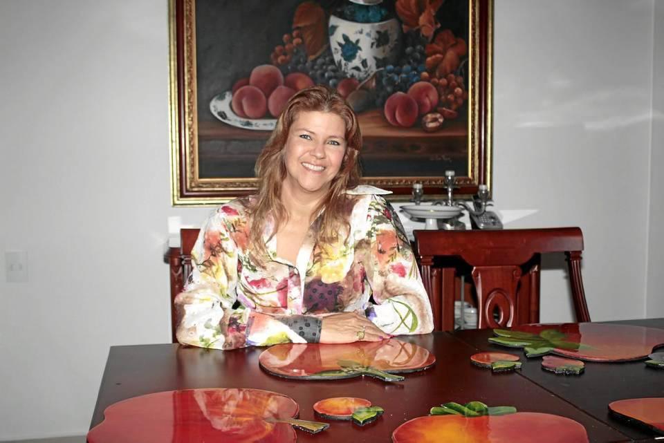 Entre las múltiples creaciones de María Consuelo están el cuadro que está detrás de ella y los individuales que se ven sobre la mesa.